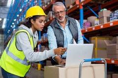Warehouse manager and female worker using laptop. In warehouse Stock Photography