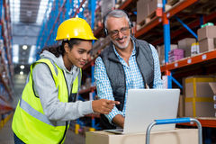 Warehouse manager and female worker using laptop. In warehouse Royalty Free Stock Image