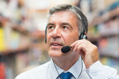 Warehouse manager giving orders on headset Royalty Free Stock Photos