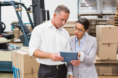 Warehouse manager and her boss working together Royalty Free Stock Photos