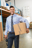 Warehouse manager holding cardboard box and scanner. In a large warehouse Stock Photos