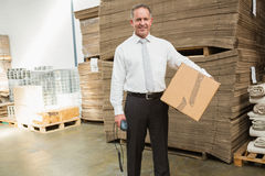 Warehouse manager holding cardboard box and scanner. In a large warehouse Royalty Free Stock Images