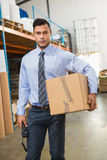 Warehouse manager holding cardboard box and scanner. In a large warehouse Stock Photography
