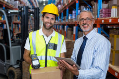 Warehouse manager holding digital tablet while male worker scanning barcode Royalty Free Stock Image