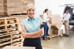Warehouse manager holding scanner with arms crossed Stock Photo