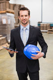 Warehouse manager holding tablet and hard hat Stock Photography