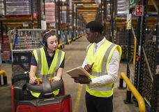 Warehouse manager instructing woman operating tow tractor stock photos