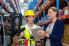 Warehouse manager with interacting female worker over digital tablet stock photography
