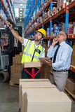 Warehouse manager interacting with male worker. In warehouse Royalty Free Stock Images