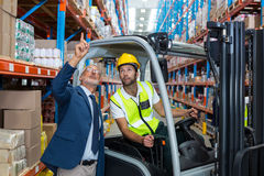 Warehouse manager interacting with male worker. In warehouse Royalty Free Stock Photo