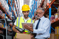 Warehouse manager with interacting male worker over digital tablet Royalty Free Stock Photos