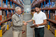 Warehouse manager and male worker interacting while working. In warehouse Stock Images