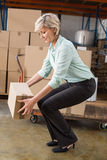 Warehouse manager picking up cardboard box. In a large warehouse Royalty Free Stock Photography