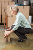 Warehouse manager picking up cardboard box. In a large warehouse Stock Image