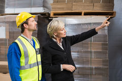 Warehouse manager pointing something to his colleagues. In a large warehouse Royalty Free Stock Images