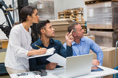 Warehouse manager pointing something to his colleagues. In a large warehouse Royalty Free Stock Photo