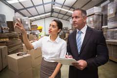 Warehouse manager showing something to her boss. In a large warehouse Stock Images