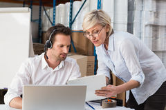 Warehouse manager showing something to her colleague Stock Photography