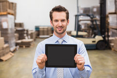 Warehouse manager showing tablet pc smiling at camera Royalty Free Stock Photos