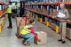 Warehouse manager showing thumbs up to female worker while carrying cardboard boxes Stock Photo