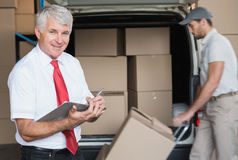 Warehouse manager smiling at camera with delivery in background Stock Image