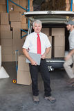 Warehouse manager smiling at camera with delivery in background Stock Photography