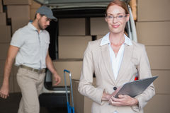 Warehouse manager smiling at camera with delivery in background Royalty Free Stock Image