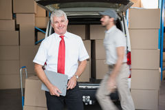 Warehouse manager smiling at camera with delivery in background Stock Photo