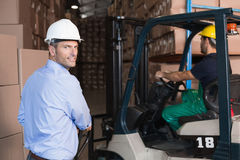 Warehouse manager smiling at camera with delivery in background Royalty Free Stock Photo