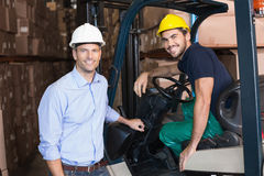 Warehouse manager smiling at camera with forklift driver Royalty Free Stock Photo