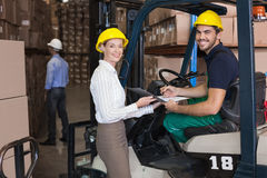 Warehouse manager smiling at camera with forklift driver Royalty Free Stock Photos