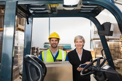 Warehouse manager smiling at camera with forklift driver Stock Photography