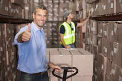 Warehouse manager smiling at camera with trolley Stock Photo