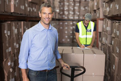 Warehouse manager smiling at camera with trolley Stock Photography
