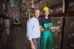Warehouse manager smiling at camera with worker Royalty Free Stock Photography