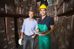 Warehouse manager smiling at camera with worker Stock Images
