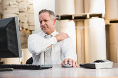 Warehouse manager suffering from shoulder pain. In a large warehouse Stock Image