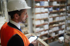 Warehouse Manager Supervising Work. Side view portrait of warehouse supervisor looking down from balcony at tall racks with packed goods holding digital tablet stock photo