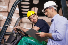 Warehouse manager talking with forklift driver Stock Photos