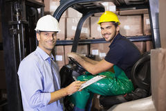 Warehouse manager talking with forklift driver Stock Image