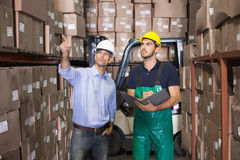 Warehouse manager talking with forklift driver Stock Photo
