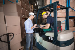 Warehouse manager talking with forklift driver Royalty Free Stock Image