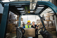 Warehouse manager talking with forklift driver Royalty Free Stock Photo