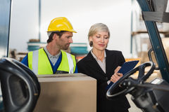 Warehouse manager talking with forklift driver Royalty Free Stock Photos