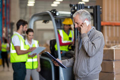 Warehouse manager talking on mobile phone and holding a clipboard Royalty Free Stock Photography