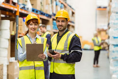 Warehouse manager talking with worker. In a large warehouse Royalty Free Stock Photo