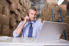 Warehouse manager using cellphone and laptop Stock Images