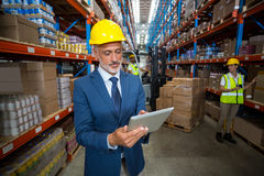 Warehouse manager using digital tablet. In warehouse Royalty Free Stock Photos