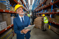 Warehouse manager using digital tablet. In warehouse Royalty Free Stock Photography