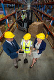 Warehouse manager using digital tablet with client and female worker. In warehouse Royalty Free Stock Photos